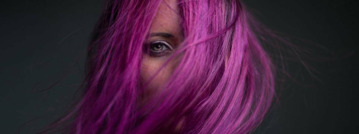 Model with purple hair covering face on a black background