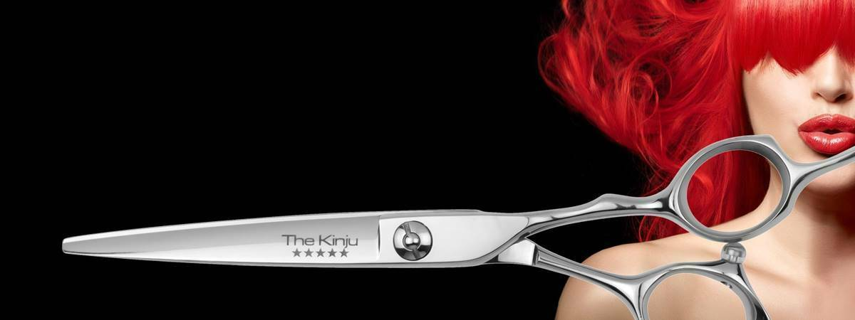 Model with red hair and hair cutting scissor on a black background
